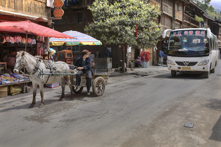 Zhaoxing Dong Village, Guizhou Province, China -  April 8, 2010:  Asian Vehicle in the country of national minorities,  shuttle bus and horse drawn transport.