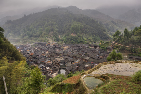 xing: Zhaoxing Dong Village, Guizhou, China -  April 7, 2010:  Peasant Village Dong ethnic minority in mountains of southwestern China, wooden huts with tiled roofs, view from above, foggy morning, spring. Stock Photo