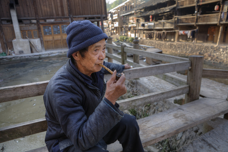 farm house: Zhaoxing Village, Guizhou, China -  April 8, 2010: Elderly Asian man in  blue dress, sitting on bench in  middle of countryside of wooden houses of ethnic minorities, with bamboo smoking pipe in hand.