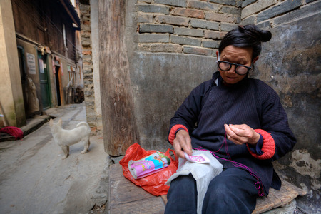 superannuated: Zhaoxing Dong Village, Guizhou Province, China -  April 9, 2010: An elderly woman in glasses is engaged in needlework outdoors, sitting on a bench near the wall of the house.