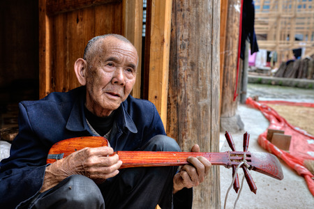 stringed: Zhaoxing Dong Village, Guizhou Province, China -  April 9, 2010: Elderly Asian men peoples Dong, playing at the local stringed musical instruments sitting on the threshold of a wooden farmhouse.
