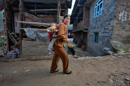 agriculturalist: Zhaoxing Dong Village, Guizhou Province, China -  April 9, 2010: Chinese woman walking on a dirt road rural street, carries the baby on her back. Editorial
