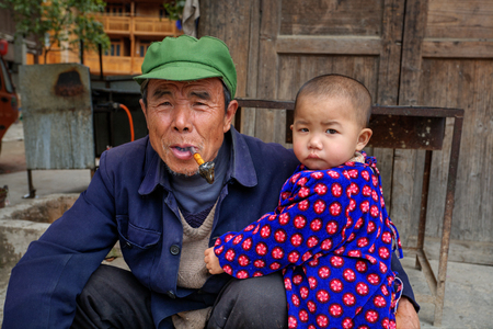 Zhaoxing Dong Village, Guizhou Province, China - April 9, 2010: Three year child hugging an elderly man who holds in his mouth pipe smoking.