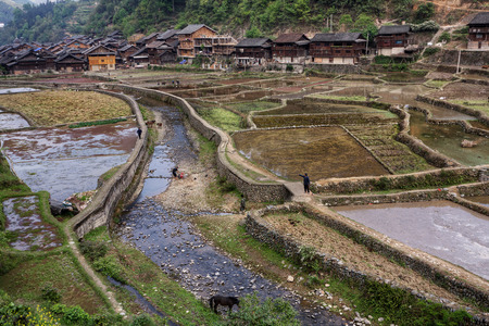 Zhaoxing Dong Village, Guizhou Province, China -  April 9, 2010: Chinese peasants poured water rice fields near the village of Dong ethnic minority. Editorial
