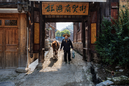 xing: Zhaoxing Dong Village, Guizhou Province, China -  April 9, 2010: Asian man wearing a hat, leads the horse by the reins, passes through the old wooden entrance gate of the village Dong ethnic minority. Editorial