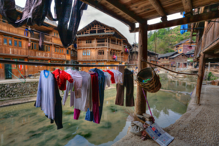agriculturalist: Zhaoxing Dong Village, Guizhou Province, China -  April 9, 2010: Erasing underwear dries on under a canopy outdoors, hanging on hanger near a rural river and wooden farmhouses local peasants. Editorial