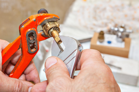 Close-up of hands plumber unscrewing plumbing fittings with adjustable wrench and red plumber pliers. Stock Photo