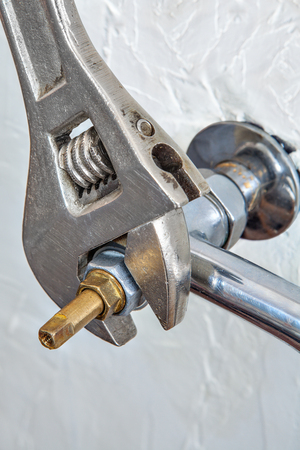 adjustable spanner: Close-up adjustable spanner plumbers screwing water faucet valve for tap.