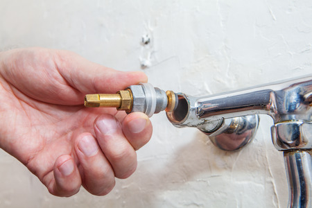hands connected: Close-up of hands plumber is connected a water tap valve to water faucet, Two handle kitchen faucet repair. Stock Photo