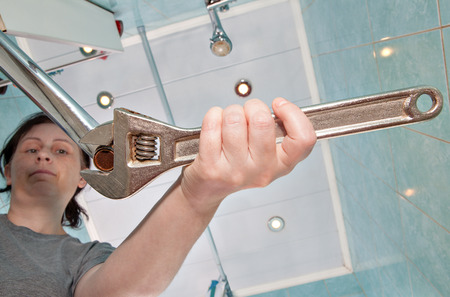Woman unscrews the old, wrong faucet aerator to sink in the bathroom, using an adjustable wrench plumber.