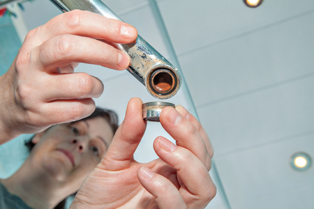 Woman replaces the old clogged aerator for faucet in the bathroom, hands handyman closeup.