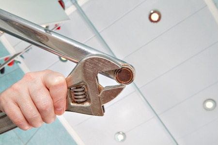 aerator: Remove old aerator from tap with an adjustable spanner, closeup.