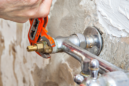 repairs: Residential repairs, replace a kitchen faucet valve, closeup of plumbers hand holding red plumbing pliers.