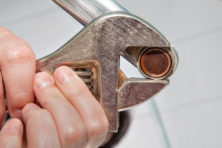 piped: Remove the old aerator from the faucet with an adjustable wrench, close-up. Stock Photo