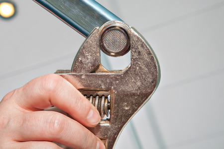 piped: Replace a Sink Aerator using an adjustable plumbing spanner , hands plumber close-up.