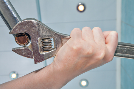 aerator: Unscrew the old wrong, clogged faucet aerator,  using an adjustable wrench plumber, hands handyman close-up. Stock Photo