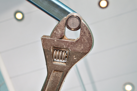 unscrewing: Fixing a Faucet Aerator,  using an adjustable wrench plumber, hands handyman close-up.