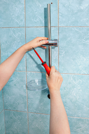 shower head: Residential plumbing repair, close-up install hand held shower head holder. Stock Photo