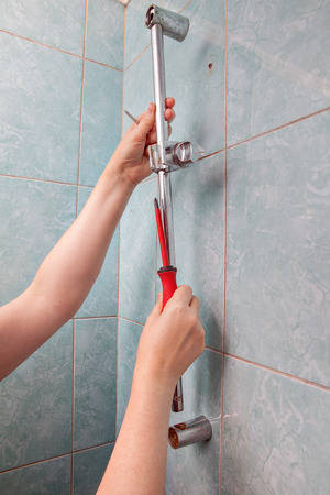 faulty: Replace broken wall mounted vertical height adjustable shower bar slider rail holder, close-up of hands remove the faulty slide rail.
