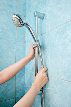 Replacing the plumbing in the bathroom, close-up human hands installed hose with  shower head in height adjustable shower bar slider rail. Stock Photo