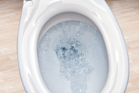 Toilet bowl  flushing water in bathroom close up.