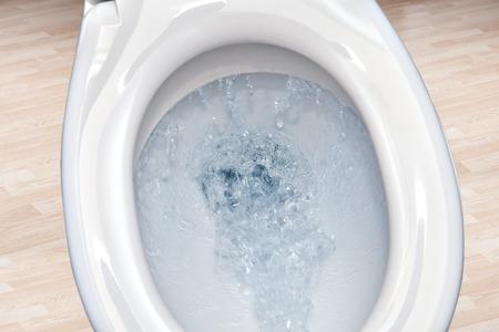 flushing: Toilet bowl  flushing water in bathroom close up.