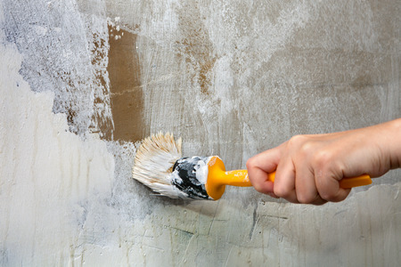 Close-up, paint brush with yellow plastic handle in a hand painter, repainting the green wall in white.