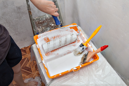 priming brush: Paints tray with whaite paint and tools used for painting, construction paintbrushes and paint rollers.