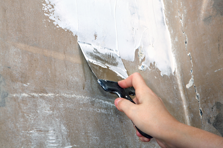 skim: Worker painter decorator, dirty putty knife in hand plasterer, close-up. Stock Photo