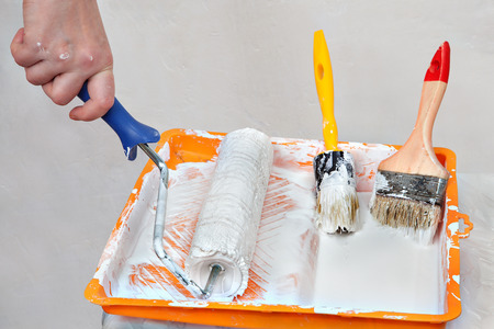 priming brush: House painting supplies, painter tools in an orange tray with white paint, roller brush and  paintbrushes.