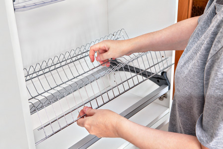 wall mounted: Assembling wall mounted shelf under kitchen cupboard with inside plate rack with drip tray, close-up of a woman hands holds wire dish rack. Stock Photo