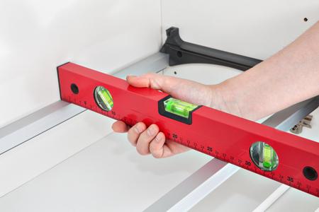 Assembling kitchen furniture, mounting shelf with dryer, handyman measuring level.