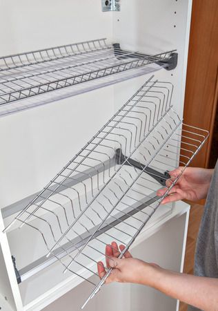 wall mounted: Install wall mounted shelf under kitchen cabinet with inside dish rack with drip tray, close-up of a woman hands holds wire part. Stock Photo