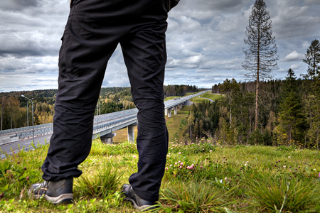 Close-up of man legs on the background of a highway viaduct crossing the forest in rural Russia.