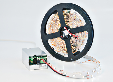 Illuminated LED diodes on a reel tape, with adapter voltage converter.
