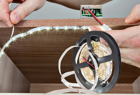 led lighting: Close-up of hands handyman paste LED tape inside the cabinet. Stock Photo