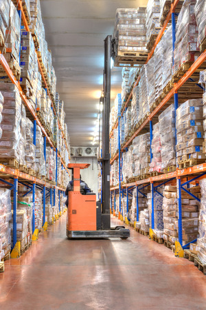 Saint-Petersburg, Russia - October 31, 2016: Cold Chain Storage Racking, deep-freeze warehouses, forklift stacker raises high pallet with goods. Editorial