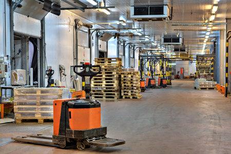 San Pietroburgo, Russia - 31 Ottobre, 2016: elettrico piattaforma pallet camion in zona bacino di caricamento all'interno del magazzino di stoccaggio a freddo.