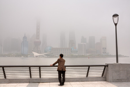 remained: Shanghai, China - April 20, 2010: Air Pollution, high-rises shrouded in heavy smog,  air in City remained severely polluted, man standing on the Bund, and looks at the Pudong District.