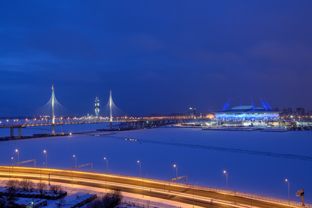 St. Petersburg, Russia - January 2, 2017: Night city in the winter, the car cable-stayed bridge, the football stadium, skyscraper under construction, and freeway.