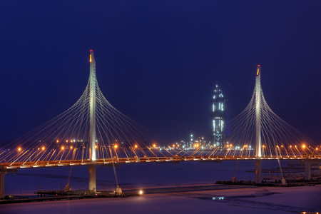 Saint-Petersburg, Russia - January 2, 2017: Night view of the Gazprom skyscraper tower under construction through the pylons of the cable-stayed bridge in the winter.