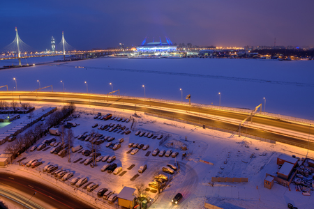 frozen river: Saint-Petersburg, Russia - January 2, 2017: Top view of a cityscape at night, cable-stayed bridge, the frozen river, a football stadium and parking lot.