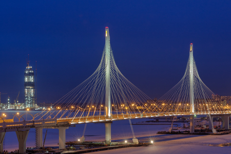 Saint-Petersburg, Russia - January 3, 2017: A highway crosses frozen river, cable bridge at night light in the winter. Editorial