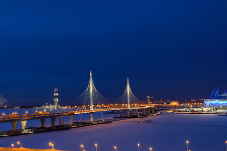 frozen river: Saint-Petersburg, Russia - January 3, 2017: A highway crosses the frozen river on a cable-stayed bridge, night view with the tower skyscraper under construction.