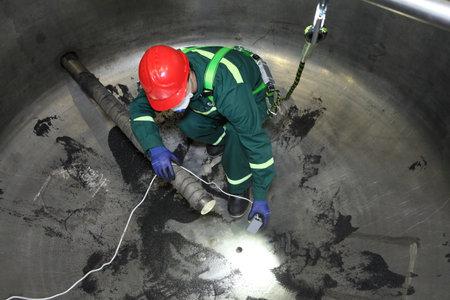 San Petersburgo, Rusia - 9 de agosto de, 2016: la inspección de calderas industriales interno, el trabajador se encuentra dentro de la caldera durante su reparación.