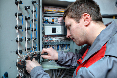 switchgear: St. Petersburg, Russia - March 5, 2013: Mechanical Engineer doing upgrade equipment electrical switchboard.