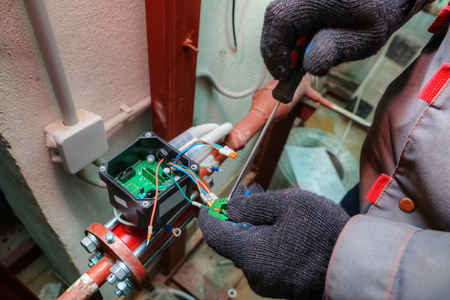 Fitter installs control devices for central heating systems in modern boiler room, hands with tool close-up.