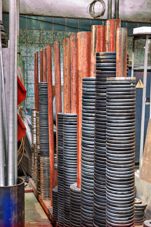 metalware: Round steel plate put on the pole in the storage facility. Stock Photo