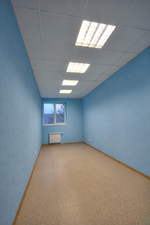 without window: Empty office with blue walls and one window.