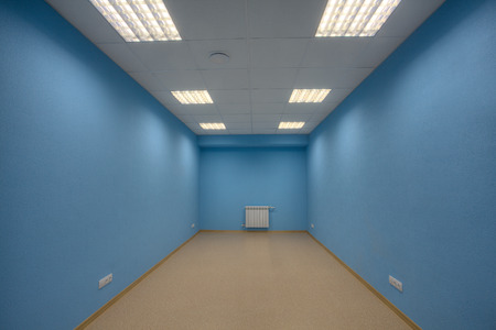 unfurnished: Small abandoned unfurnished office, no body, and no windows, the walls are painted in blue.